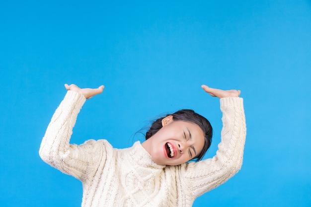 Schöne frau, die einen neuen langärmeligen weißen teppich, eine geste auf einem blau zeigend trägt. handeln. Kostenlose Fotos