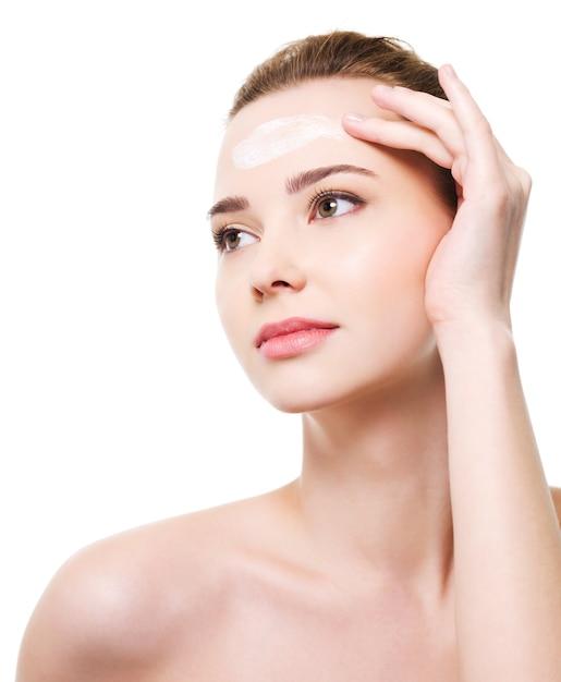 Schöne frau, die feuchtigkeitscremekosmetik auf stirn anwendet Kostenlose Fotos