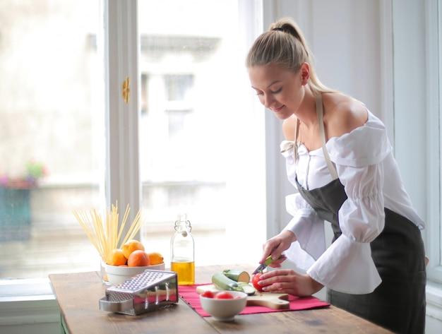 Schöne frau, die gemüse an der küche schneidet Kostenlose Fotos