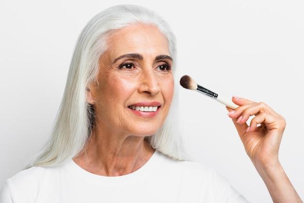 Schöne frau, die ihr make-up tut Kostenlose Fotos