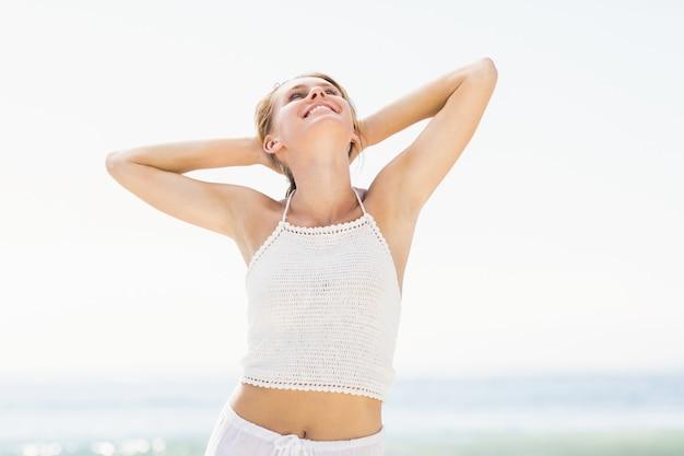 Schöne frau, die ihre arme auf dem strand ausdehnt Premium Fotos
