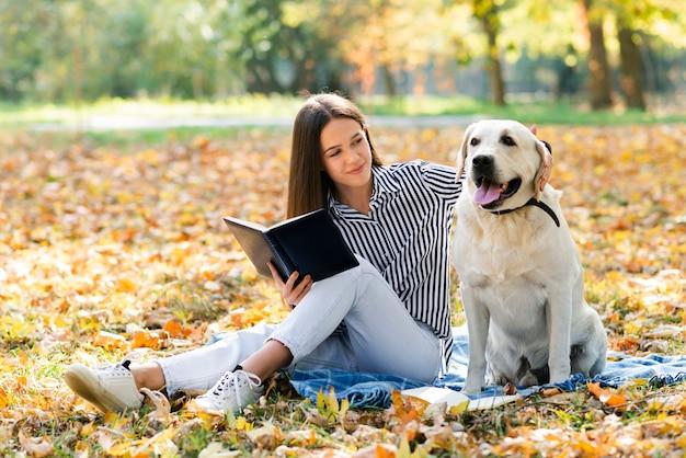 Schöne frau, die ihren hund streichelt Kostenlose Fotos