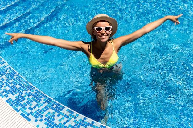 Schöne frau, die im pool aufwirft | Kostenlose Foto