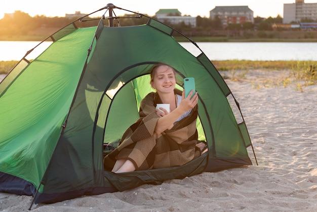 Schöne frau, die im zelt sitzt und ein foto macht. camping in der nähe von wasser. urlaub im freien. Premium Fotos