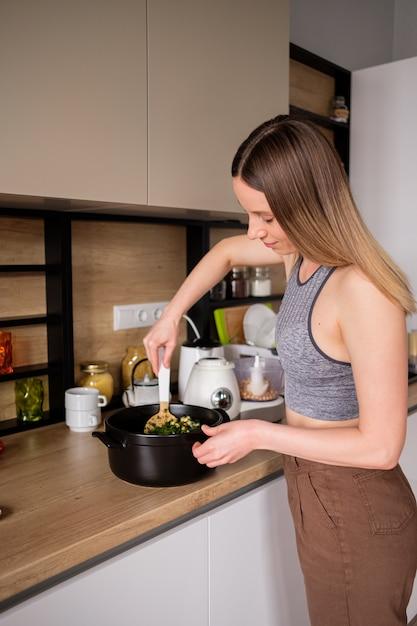 Schöne frau, die in der modernen küche kocht Kostenlose Fotos