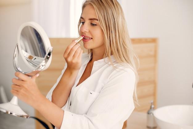 Schöne frau, die in einem badezimmer steht Kostenlose Fotos