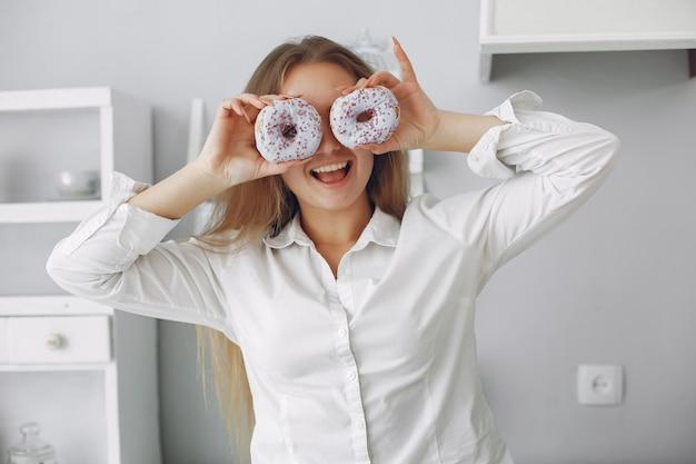 Schöne frau, die in einer küche mit krapfen steht Kostenlose Fotos