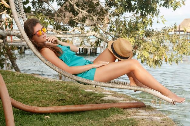 Schöne frau, die in sunbed sich entspannt Premium Fotos