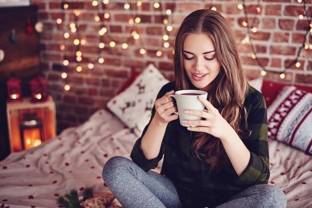 Schöne frau, die kaffee in ihrem schlafzimmer trinkt Kostenlose Fotos