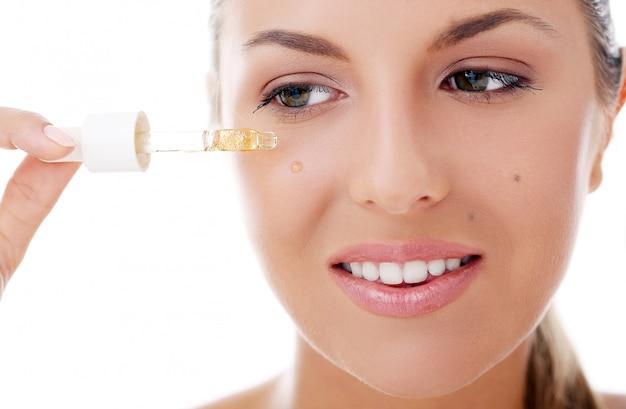 Schöne frau, die kosmetik aufträgt Kostenlose Fotos