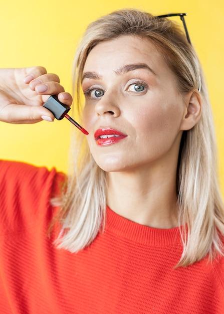 Schöne frau, die lippenstiftabschluß oben anwendet Kostenlose Fotos