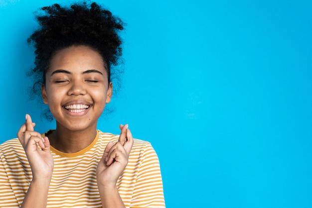 Schöne frau, die mit den fingern gekreuzt lächelt und aufwirft Kostenlose Fotos