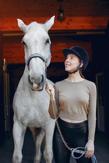 Schöne frau, die mit einem pferd steht | Kostenlose Foto