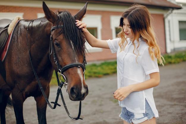 Schöne frau, die mit einem pferd steht Kostenlose Fotos