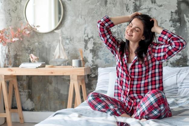 Schöne frau, die morgen im pyjama genießt Kostenlose Fotos