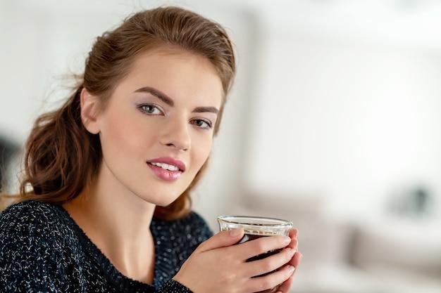 Schöne frau, die morgens zu hause kaffee trinkt Kostenlose Fotos
