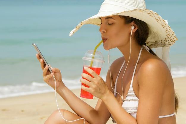 Schöne frau, die musik am strand hört Premium Fotos