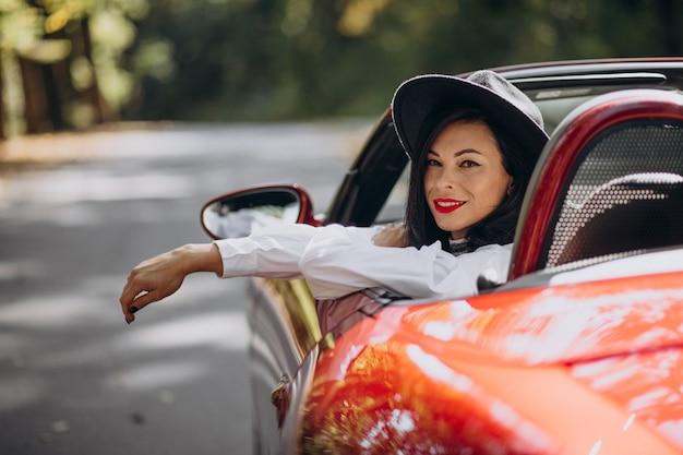 Schöne frau, die rotes cabrio fährt Kostenlose Fotos