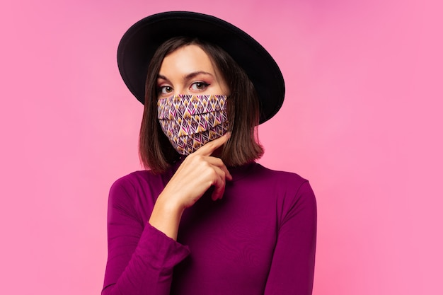 Schöne frau, die stilvolle schützende gesichtsmaske trägt. schwarzer hut Kostenlose Fotos