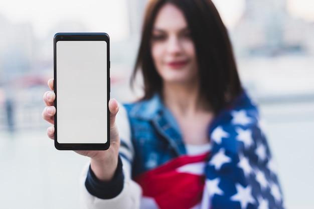 Schöne frau, die telefon mit weißem bildschirm zeigt Kostenlose Fotos