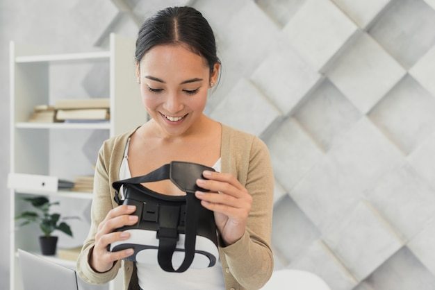 Schöne frau, die virtuellen kopfhörer betrachtet Kostenlose Fotos