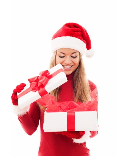 Schöne frau, die weihnachtsgeschenk öffnet Kostenlose Fotos