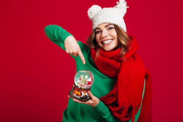 Schöne frau, die weihnachtsspielzeug anhält Kostenlose Fotos