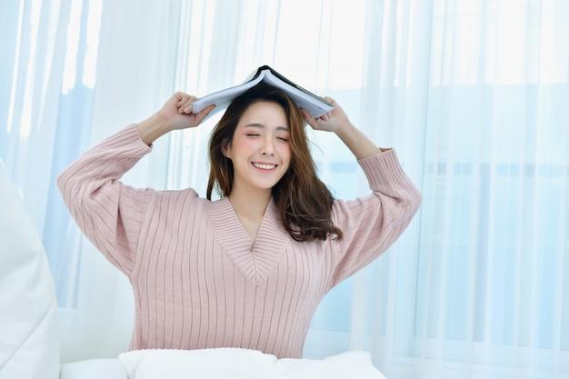 Schöne frau entspannt sich in einem weißen schlafzimmer. Premium Fotos