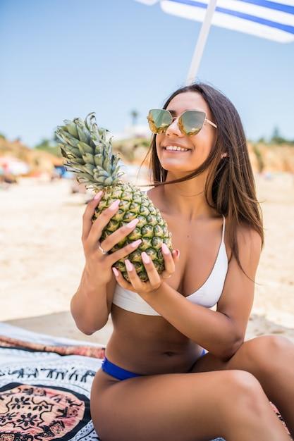 Schöne frau hält ananas in den händen eines entspannten strandtropen. schönes weibliches modell mit tropischen früchten in ihren händen Kostenlose Fotos