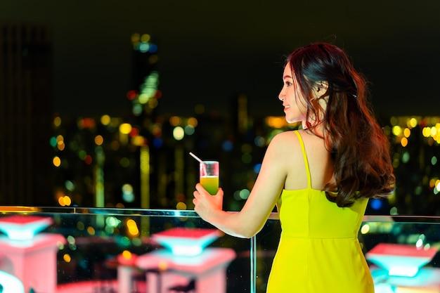 Schöne frau im abendkleid, das cocktail über nachtstadt hält Premium Fotos