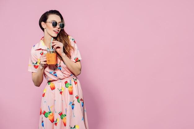 Schöne frau im bunten kleid mit bedruckten fritten, die mit glas saft aufwerfen Premium Fotos