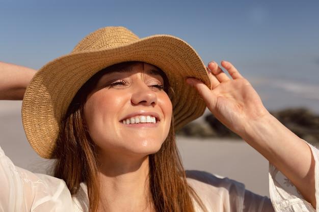 Schöne frau im hut, der weg auf strand im sonnenschein schaut Kostenlose Fotos