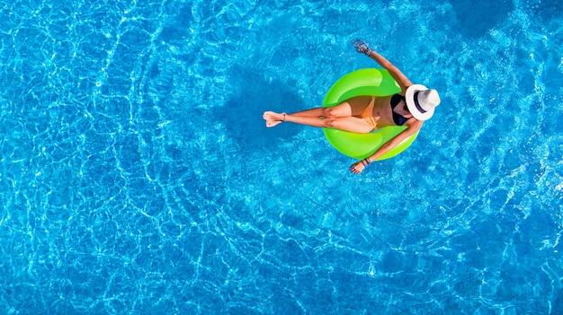Schöne frau im hut im schwimmbad auf aufblasbarem ring im wasser im urlaub Premium Fotos