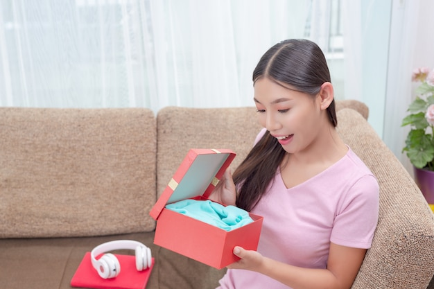 Schöne frau im rosafarbenen kleid, sitzend auf dem sofa und öffnen eine geschenkbox. Kostenlose Fotos