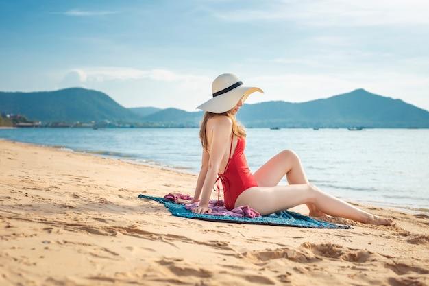 Schöne frau im roten badeanzug sitzt am strand Premium Fotos