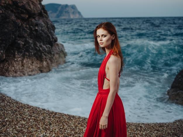 Schöne frau im roten kleid strand ozean landschaft wellen. Premium Fotos