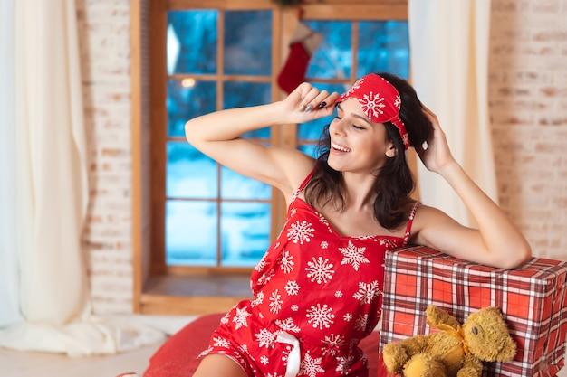 Schöne frau im schlafanzug mit geschenkbox Kostenlose Fotos