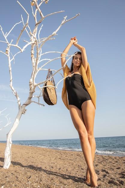 Schöne frau im schwarzen badeanzug am strand Premium Fotos