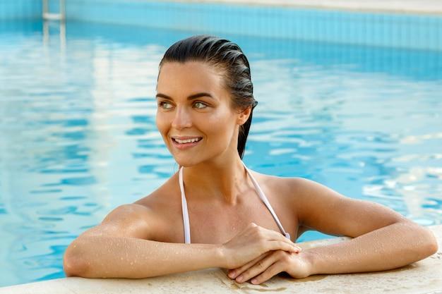 Schöne frau im schwimmbad Premium Fotos