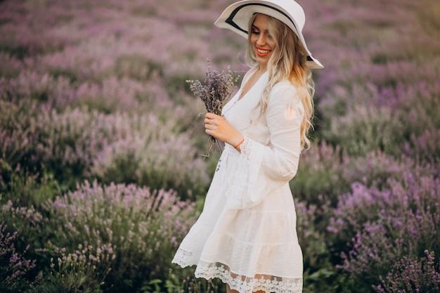 Schöne frau im weißen kleid in einem lavendelfeld Kostenlose Fotos