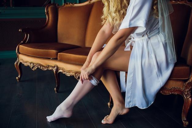 Schöne frau in der weißen wäsche, die auf bett in ihrem schlafzimmer sitzt und auf strümpfe sich setzt. Premium Fotos