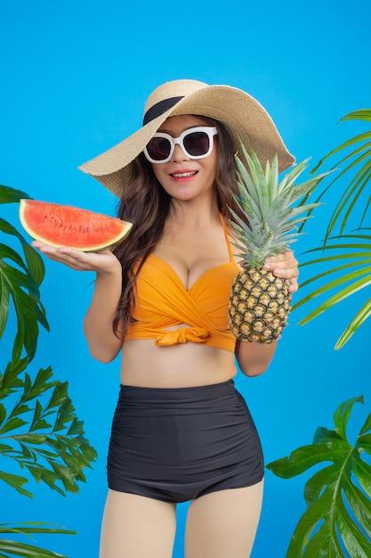 Schöne frau in einem badeanzug, der ananas und wassermelone auf blau hält Kostenlose Fotos