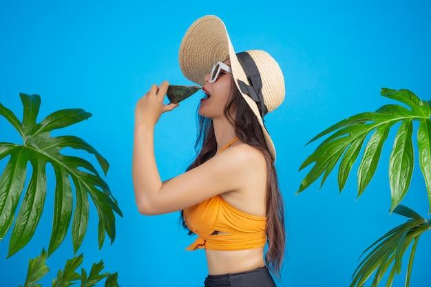 Schöne frau in einem badeanzug, der eine wassermelone auf blau anhält Kostenlose Fotos