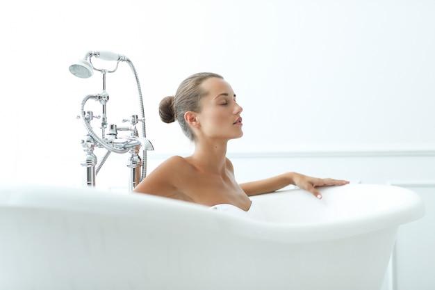Schöne frau in einem badezimmer Kostenlose Fotos