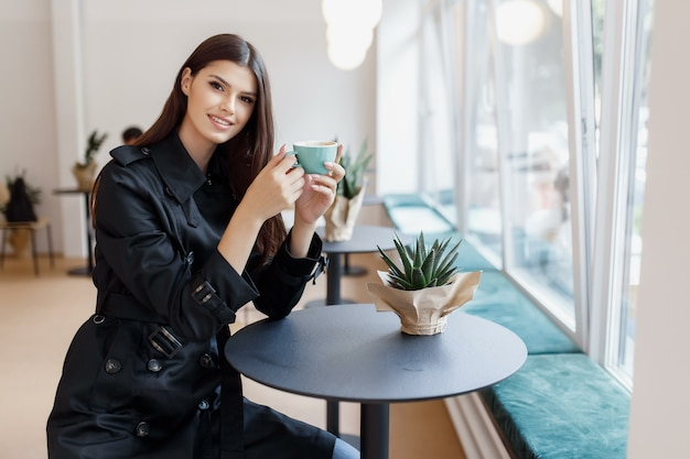 Schöne frau in einem café mit einer tasse kaffee Premium Fotos