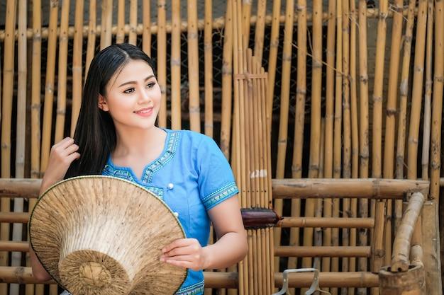 Schöne frau in einem traditionellen thailändischen kleid, blau in einer rustikalen thailändischen atmosphäre Premium Fotos