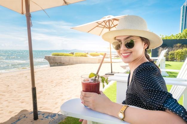 Schöne frau ist entspannend am strand, unter sonnenschirm Premium Fotos