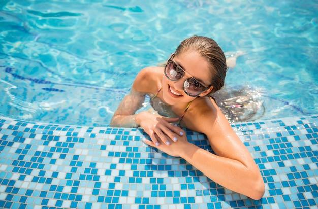 Schöne frau ist im swimmingpool entspannend. Premium Fotos
