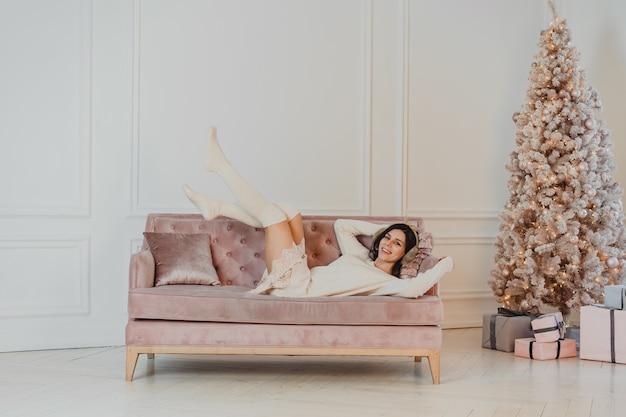 Schöne frau liegt auf dem sofa. Kostenlose Fotos