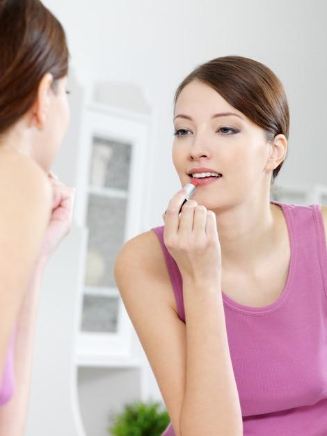 Schöne frau malt ihre lippen mit lippenstift, der in den spiegel zu hause schaut Kostenlose Fotos